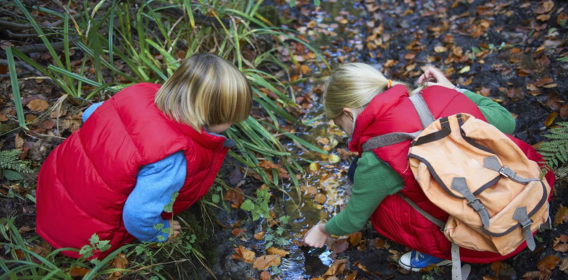 Boy and girl piking up leaves from a stream