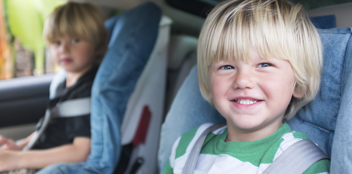 Two brothers sitting in their car seats smiling.