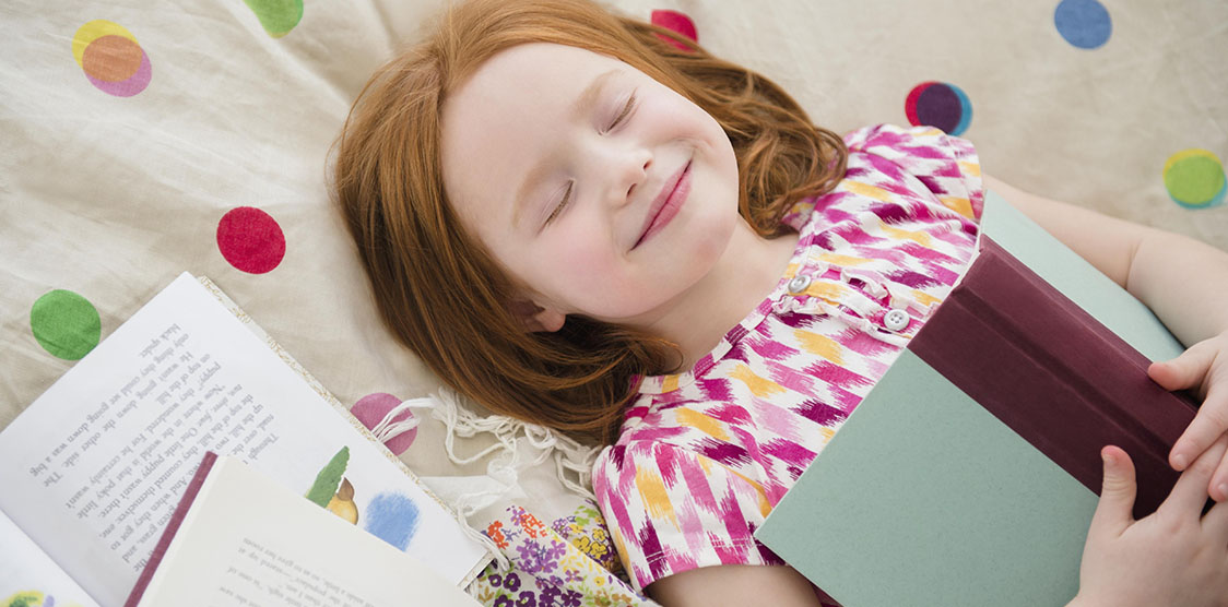 Little girl lying on bed surrounded by books