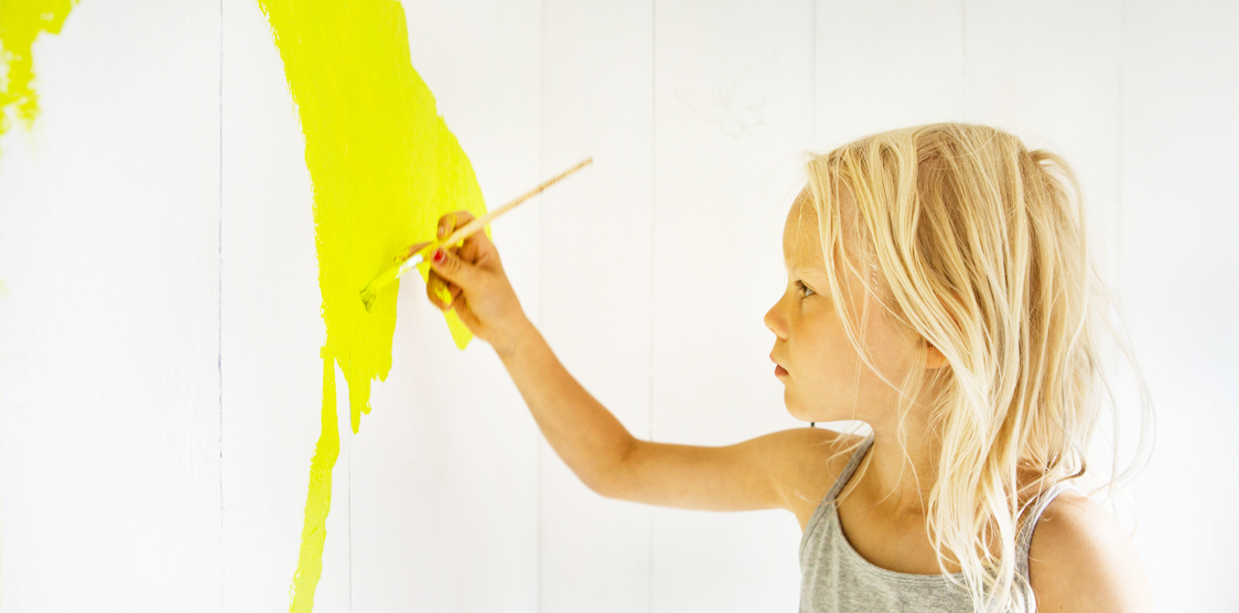 A toddler painting the wall with yellow non toxic paint.