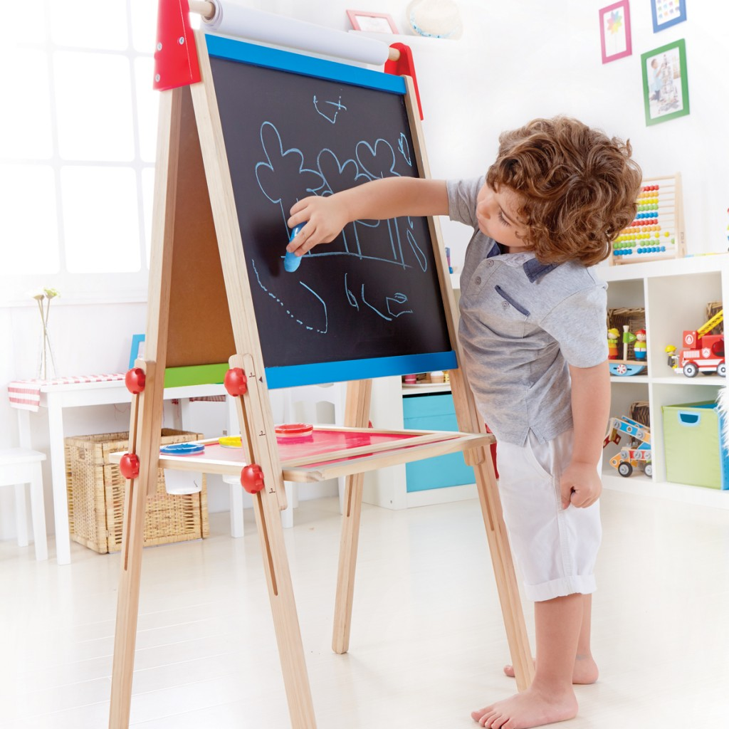 A little boy using chalk on the Hape double sided kids easel