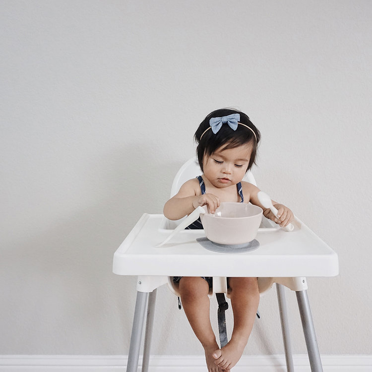 little girl sitting in highchair looking at bowl