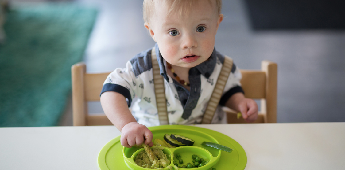 little boy eating vegetables on non toxic baby plate