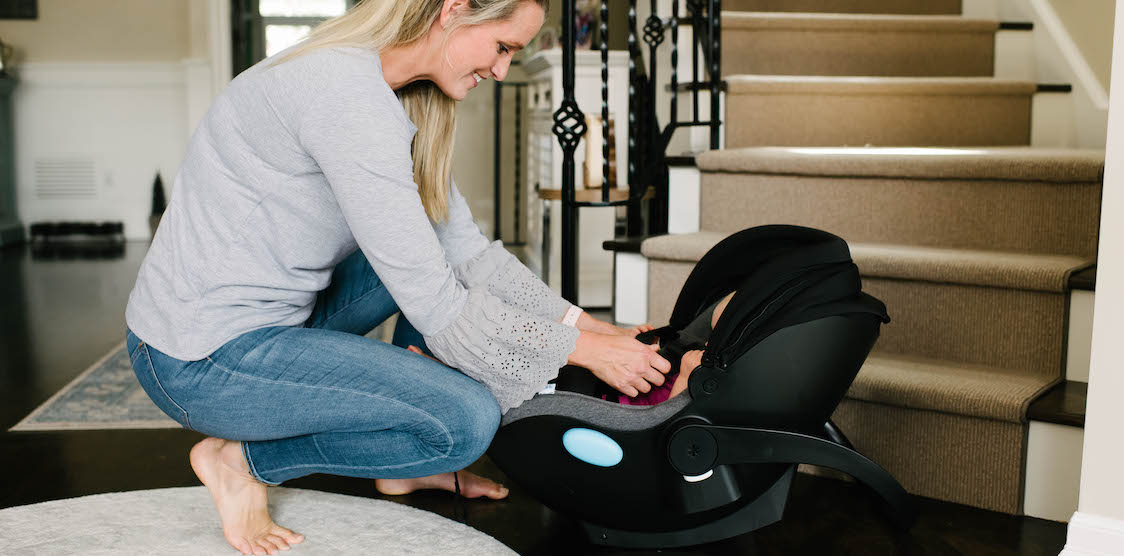 A mother putting her child in the Clek Liing Infant Car Seat