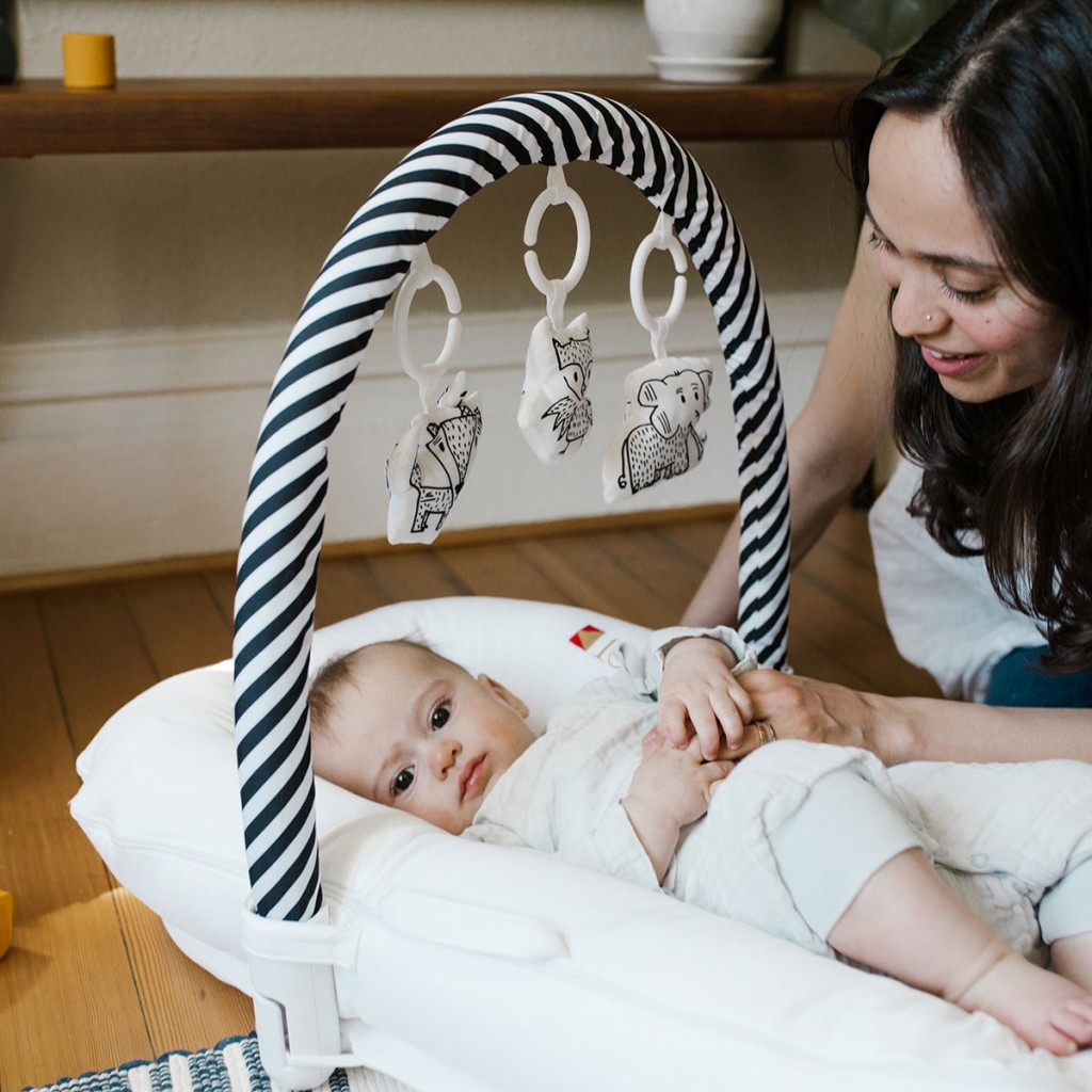 DockATot Toy Arch in Black & White Stripe with baby