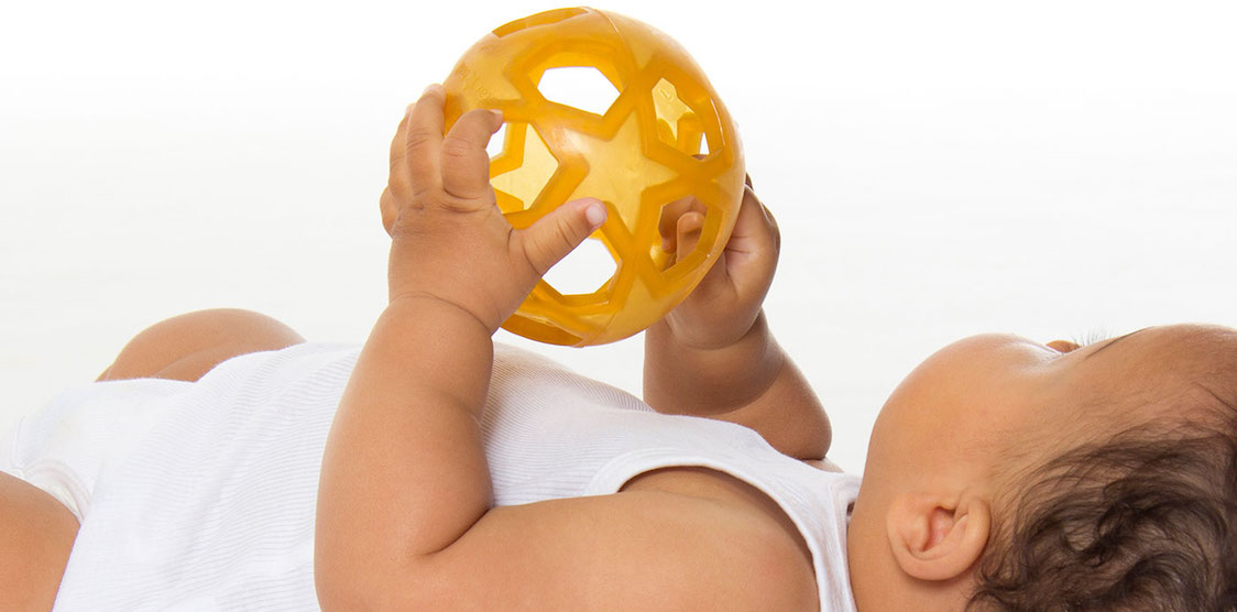 A baby playing with the Hevea sensory rubber star ball