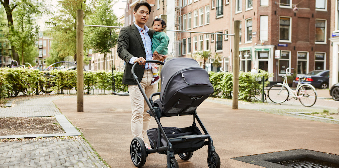A dad holding his toddler and pushing his baby in the Nuna MIXX stroller