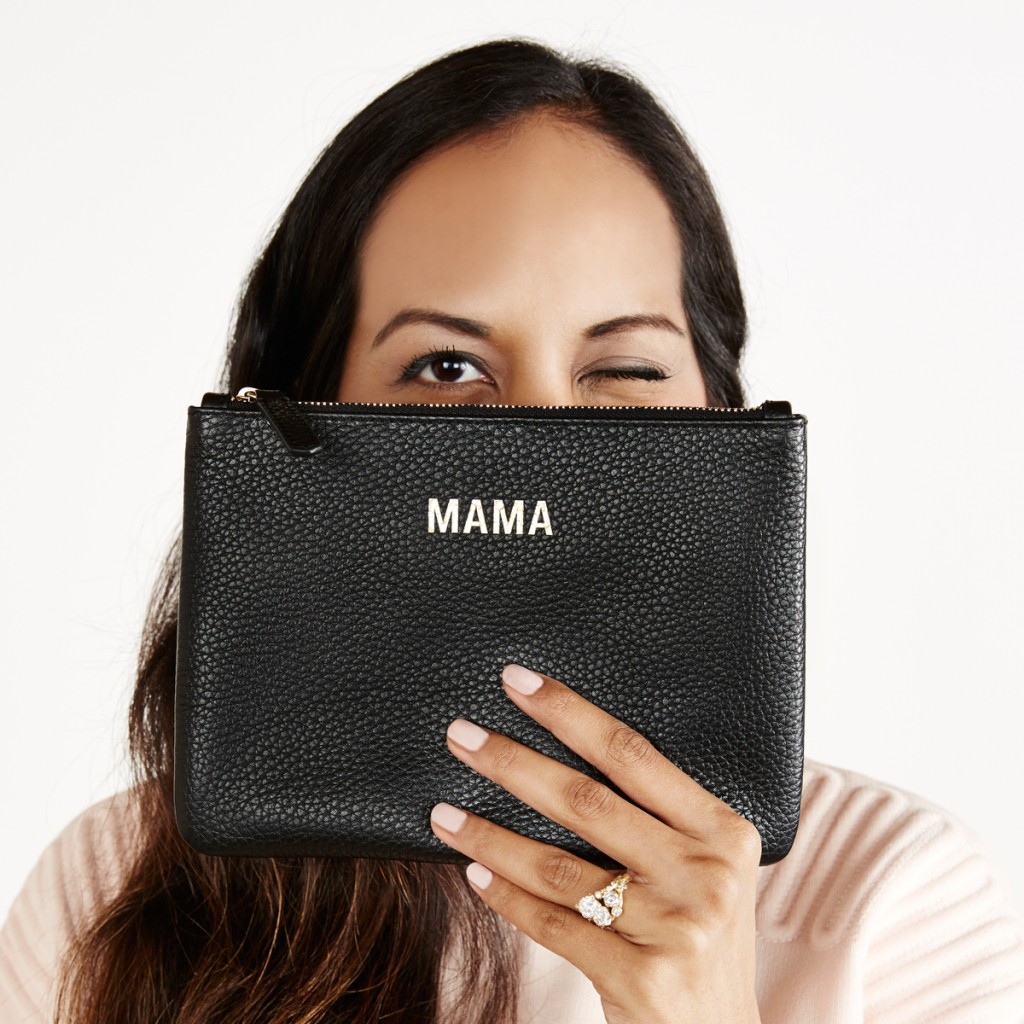 A woman holding the Jem & Bea Mama Clutch in front of her face