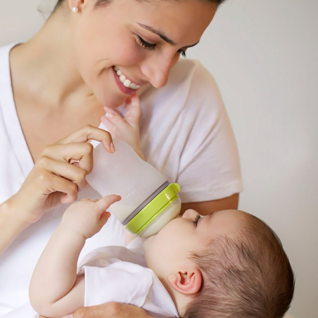 A woman using a comotomo bottle to feed her baby