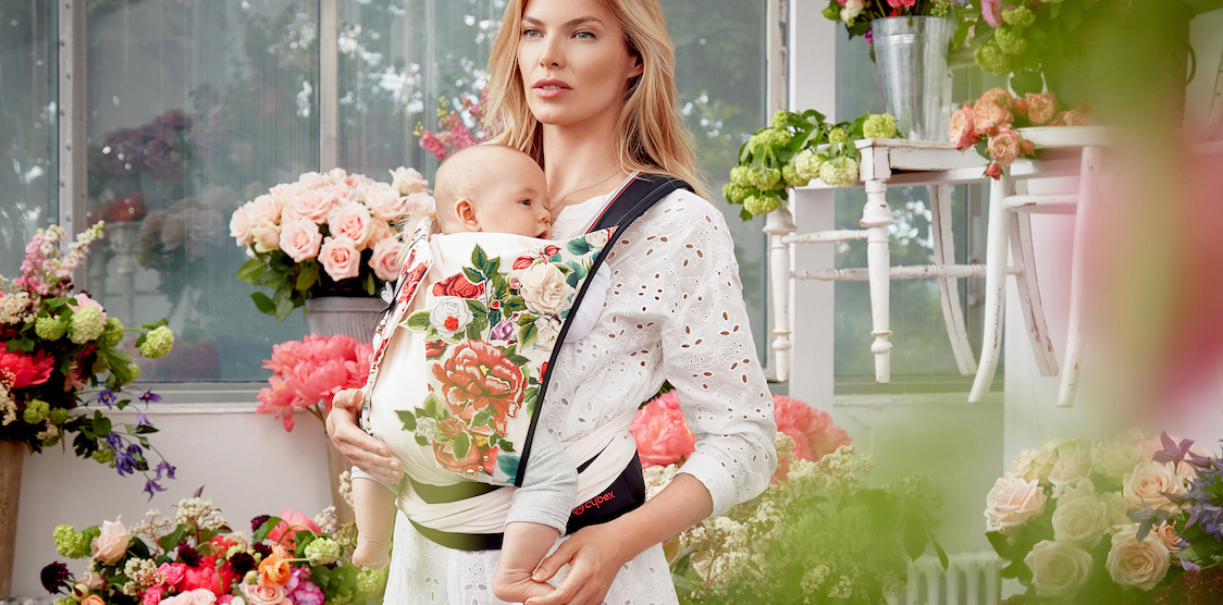 A woman wearing a baby in a Cybex Spring Blossom carrier