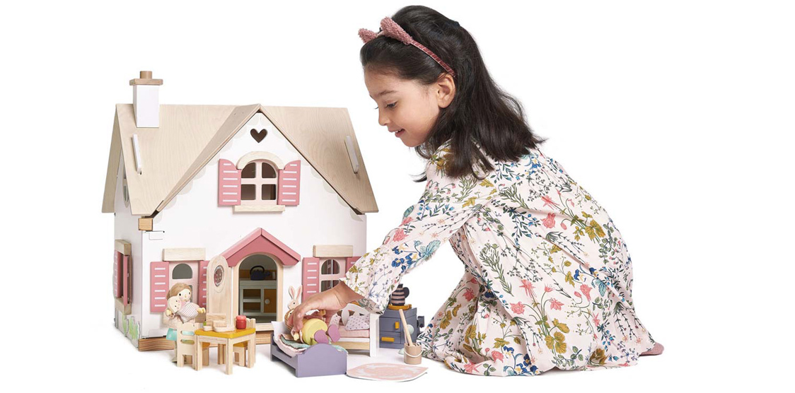 little girl playing with wooden doll house