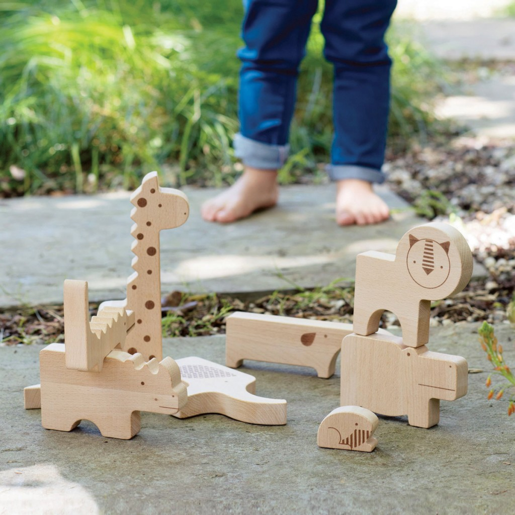 A child playing with Petit Collage wooden safari themed blocks