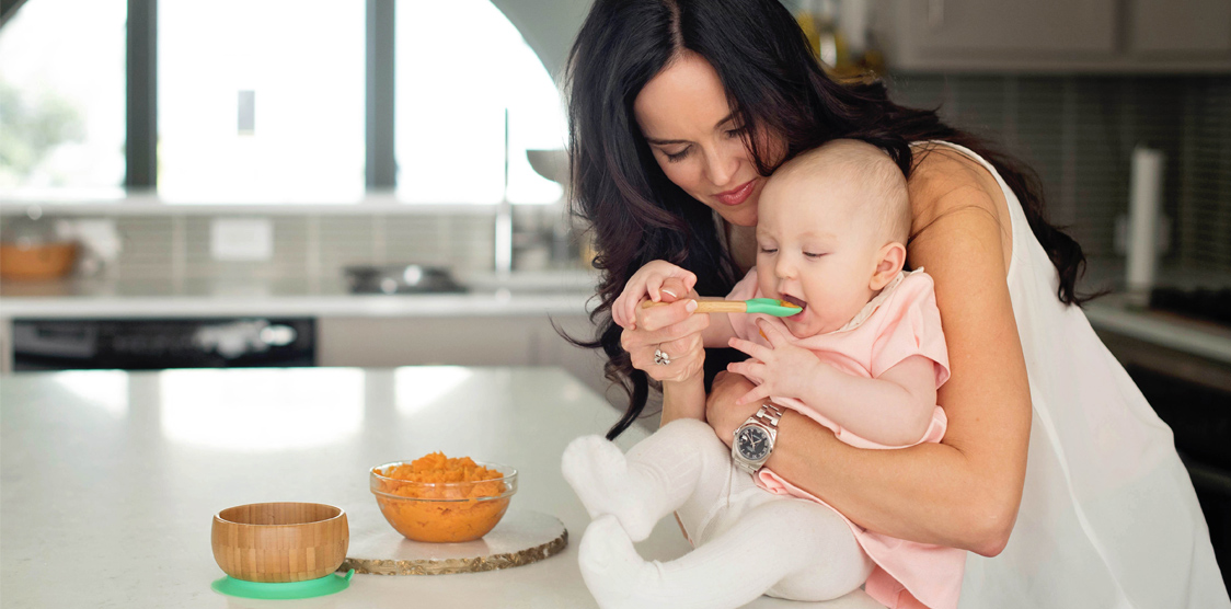 Mom feeds mashed sweet potatoes to baby at an age where she can start eating baby food.