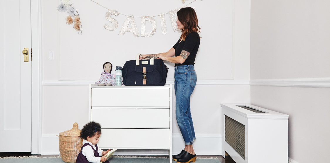 mom packing travel bag with baby