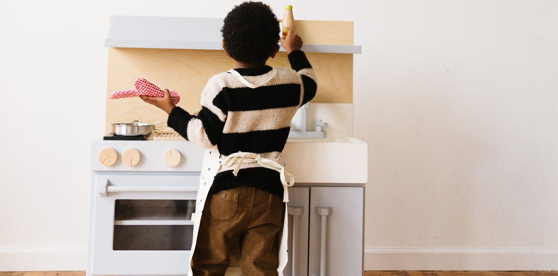 child playing with wooden kitchen set