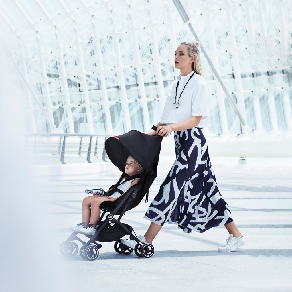A woman pushing a child in a GB Pockit Plus Travel Stroller