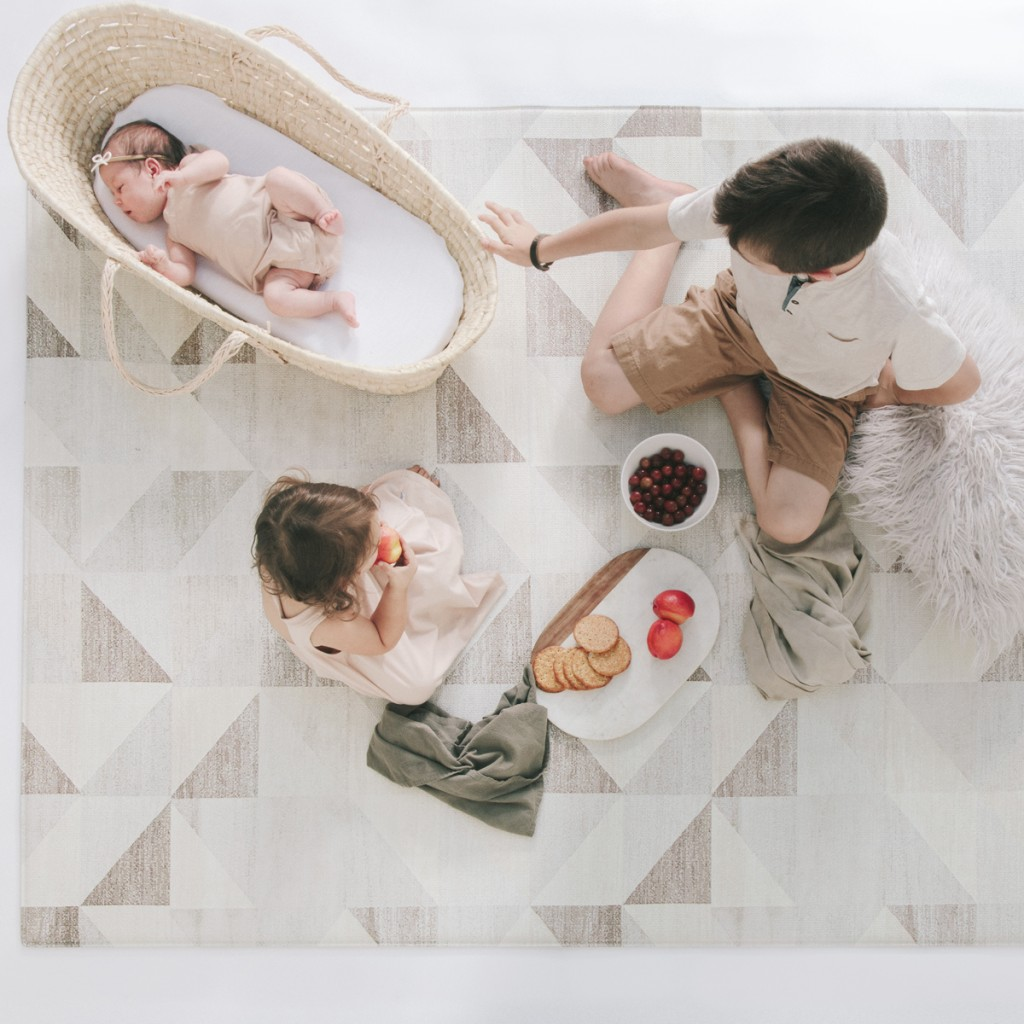 Three kids playing on a ruggish play rug