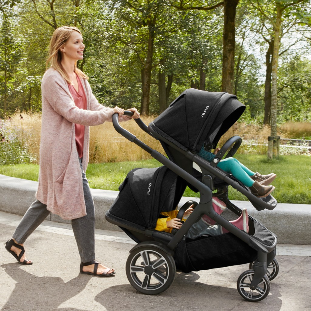 A woman pushin her kids in a nuna demi grow stroller