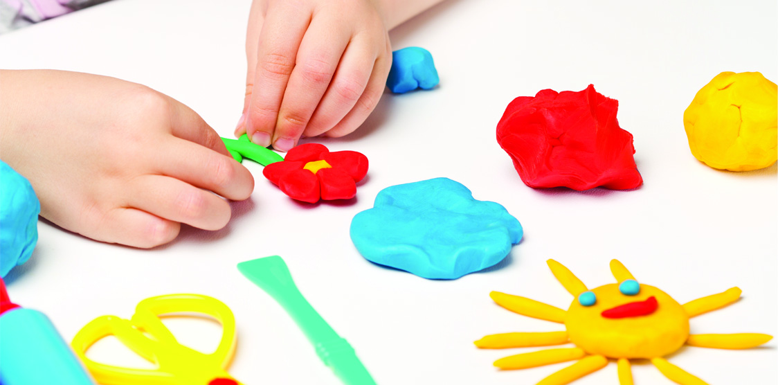 Child rolling dough for sensory play