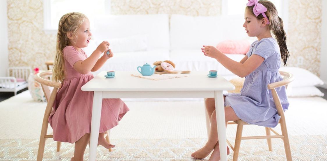 two little girls sitting at a table having tea party