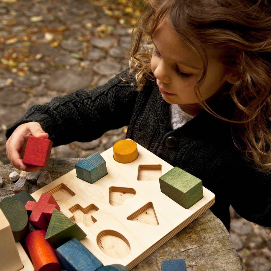 Child playing with the wooden story shape puzzle