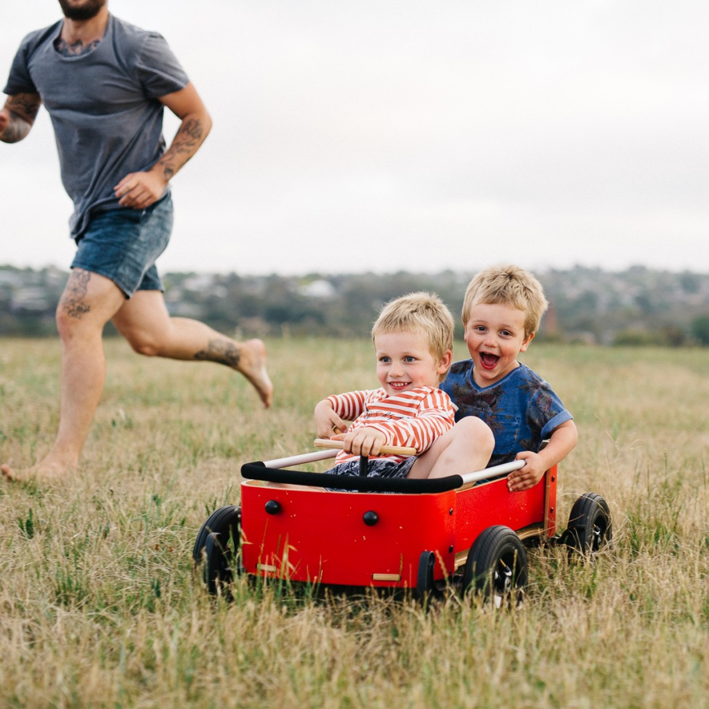 two kids riding in a red wishbone wagon