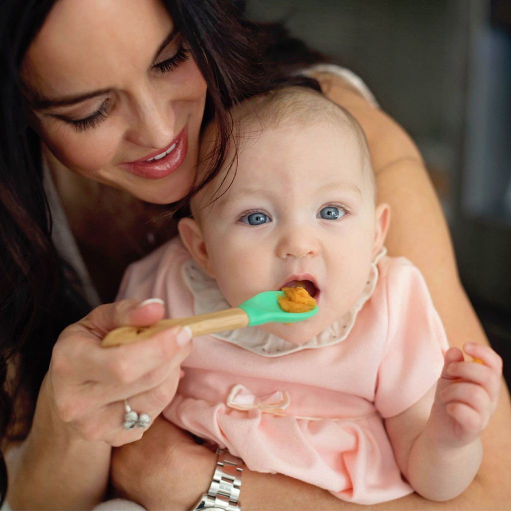 A mother feeding a baby with a bamboo and silicone avanchy spoon