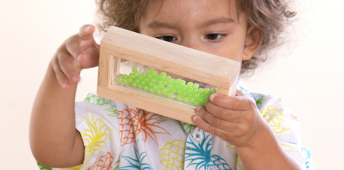 A two year old playing with guidecraft's wooden sensory blocks