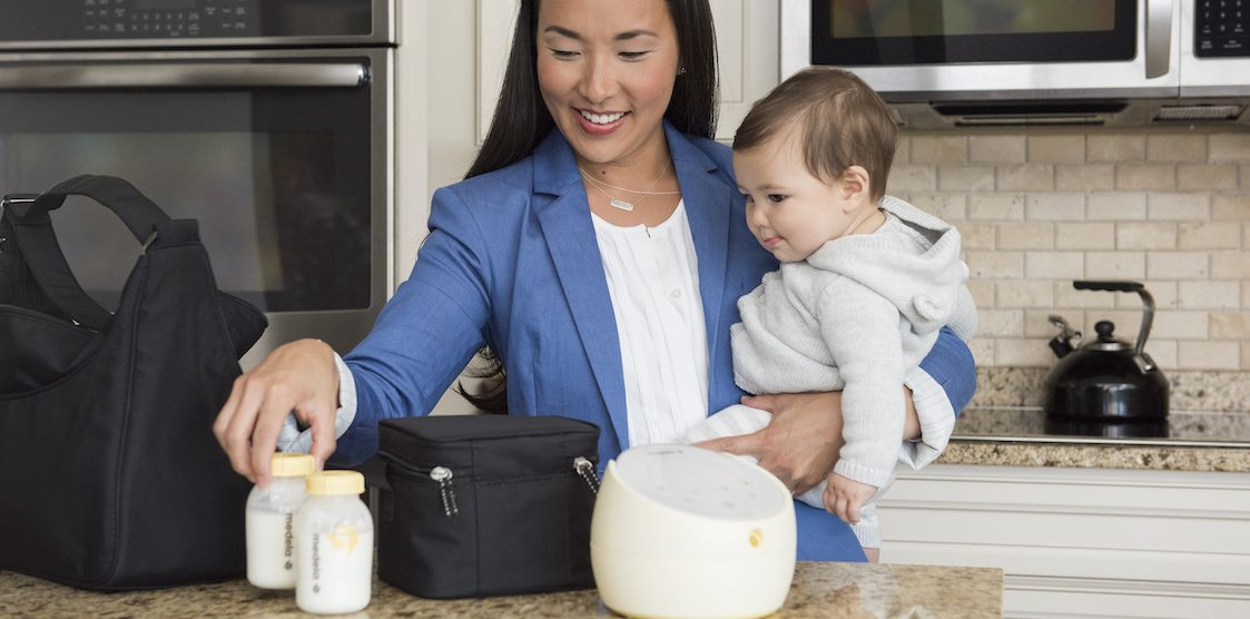A woman holding her baby while packing her Medela Sonata Breastmilk Pump and bottles