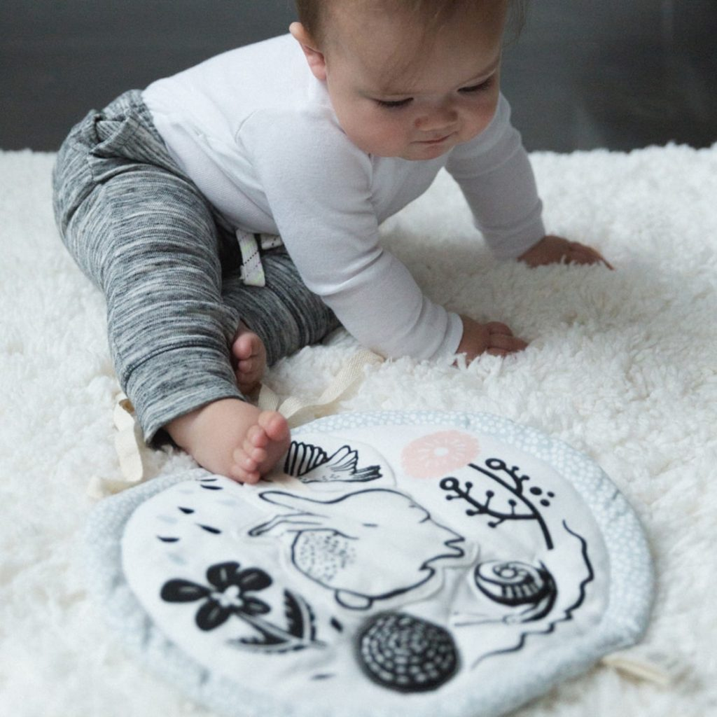 A baby playing with the Wee Gallery Meadow Activity pad