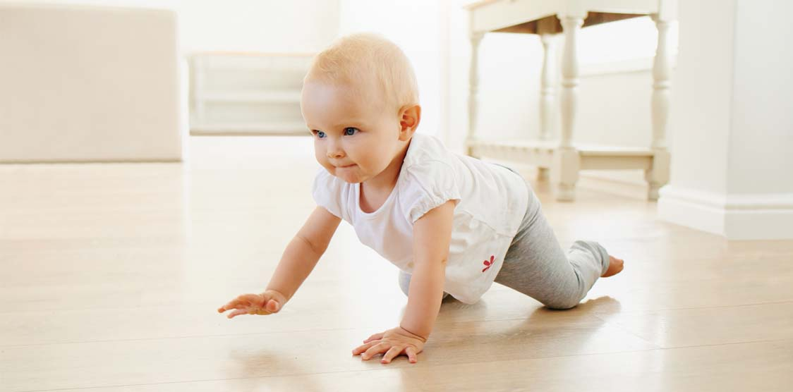 A 6 month old baby crawling.