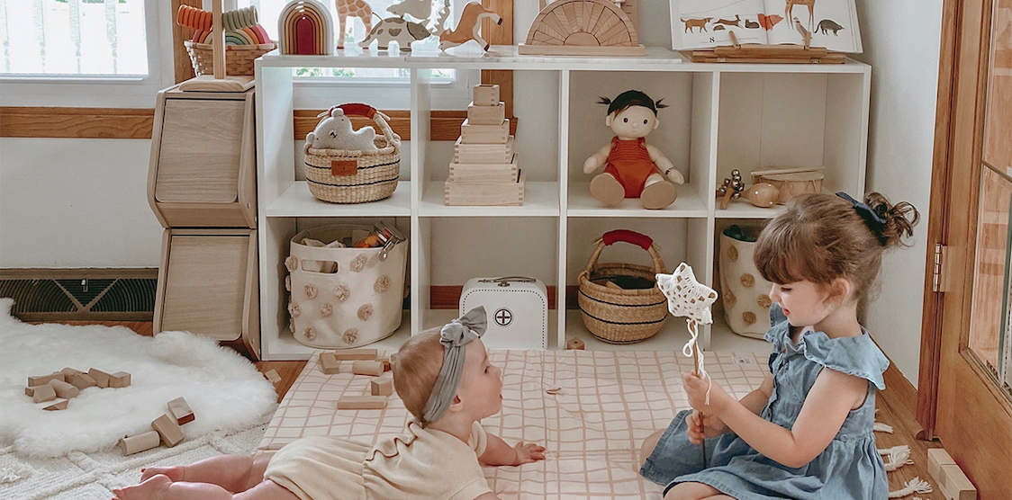 Two kids playing in a small playroom on a toki mat
