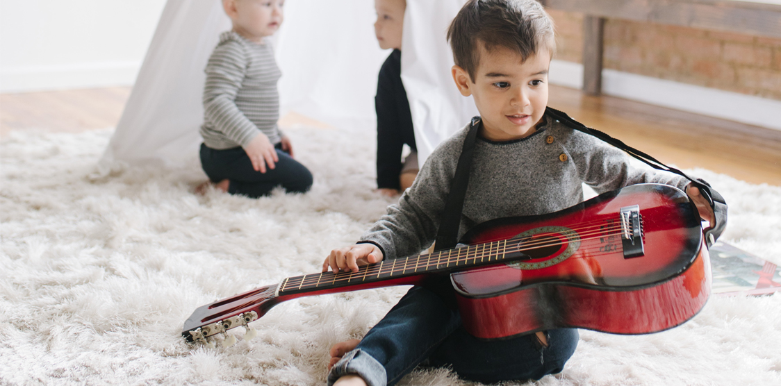 little boy with a guitar christmas present