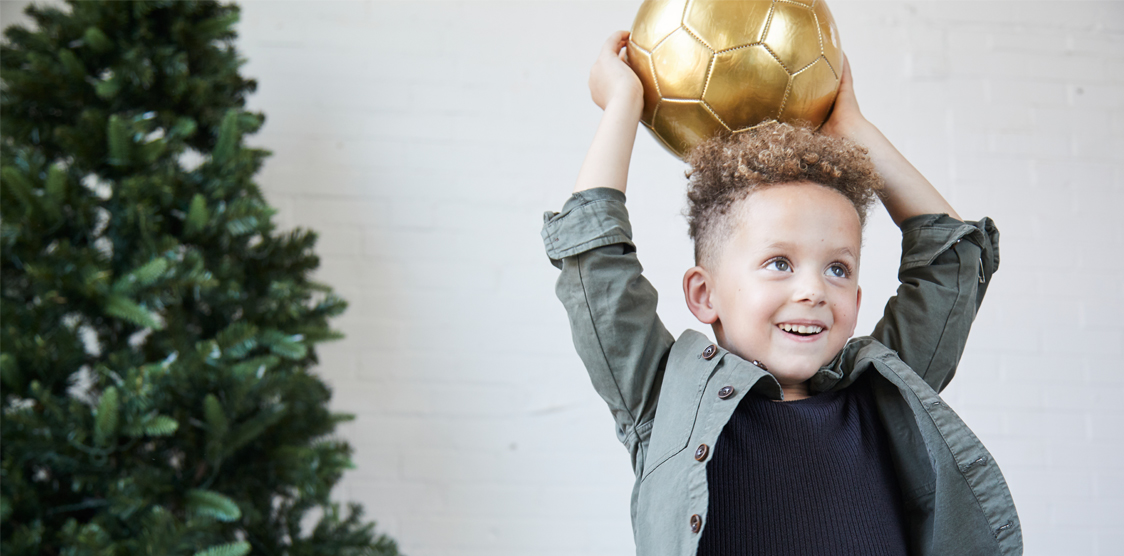 Child playing with a KAOS Midas Gold Soccer Ball