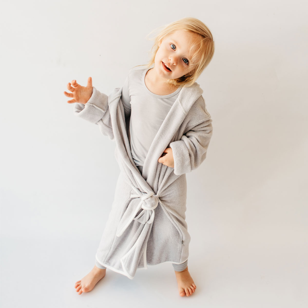 Kyte Baby Hooded Bamboo Terry Bath Robe in Storm Grey with Cloud White on girl