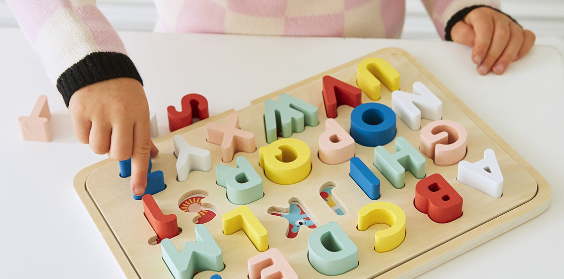 child playing with an educational alphabet puzzle