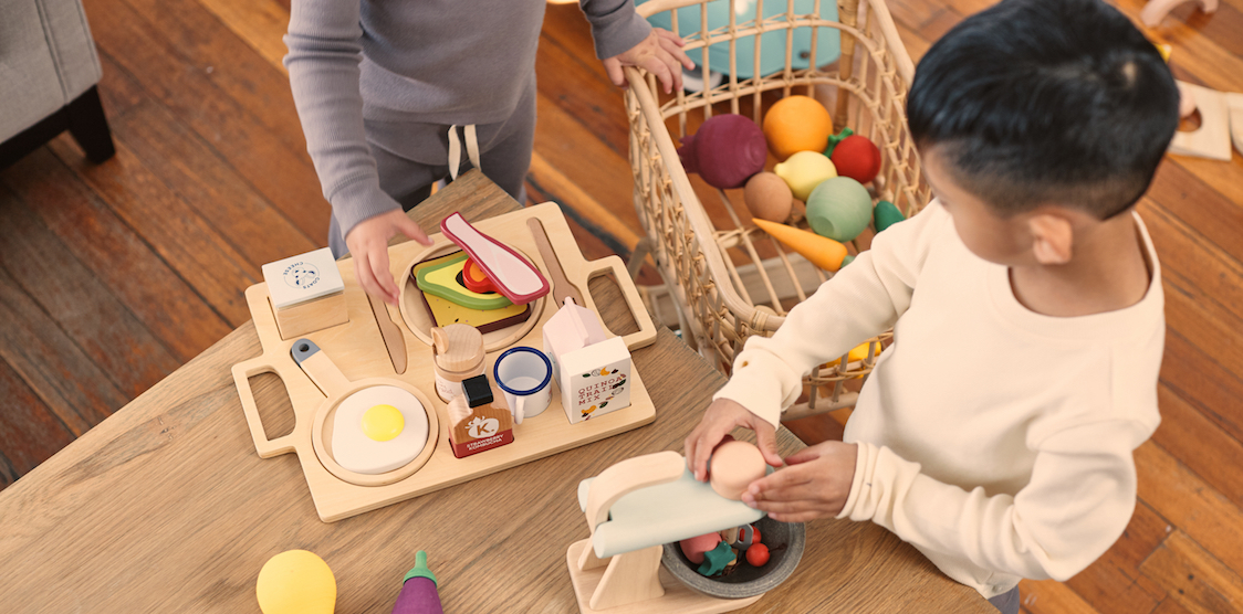 Two boys playing with the Make Me Iconic breakfast tray and Raduga Grez wooden vegetable play set