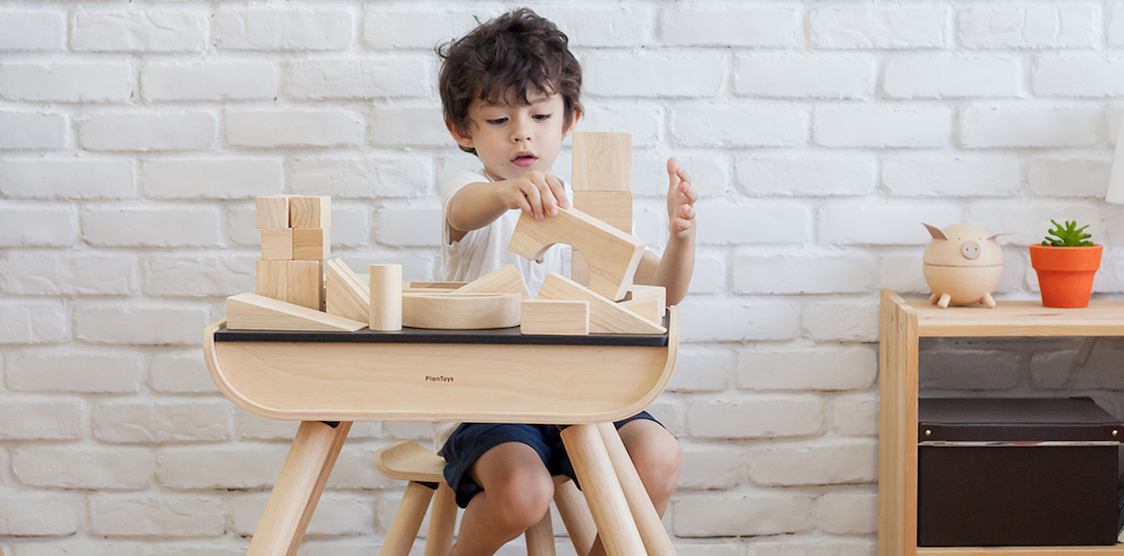 A child playing with PlanToys blocks at a desk