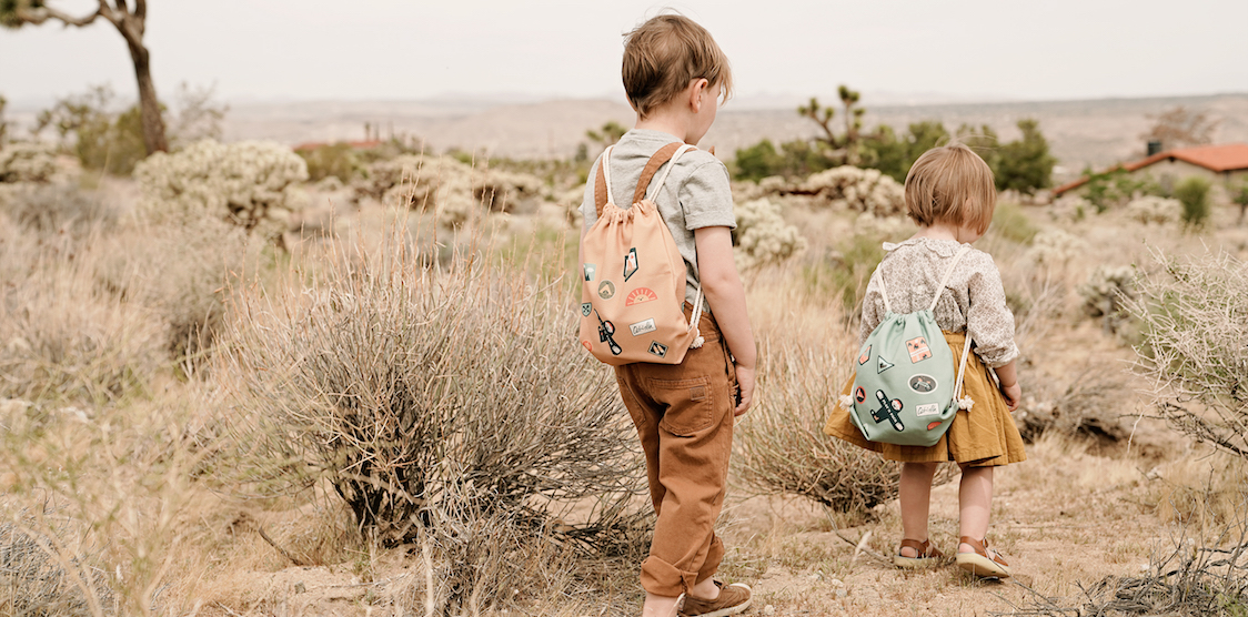 Two kids playing with Olli Ella Play'N Pack art backpacks