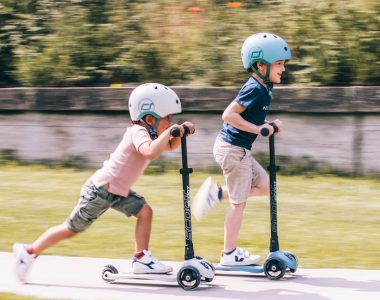 Two kids riding scooters