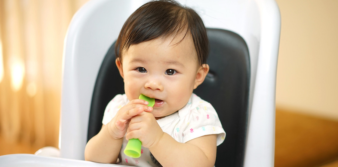 A baby using the olababy 5 piece feeding starter set to wean