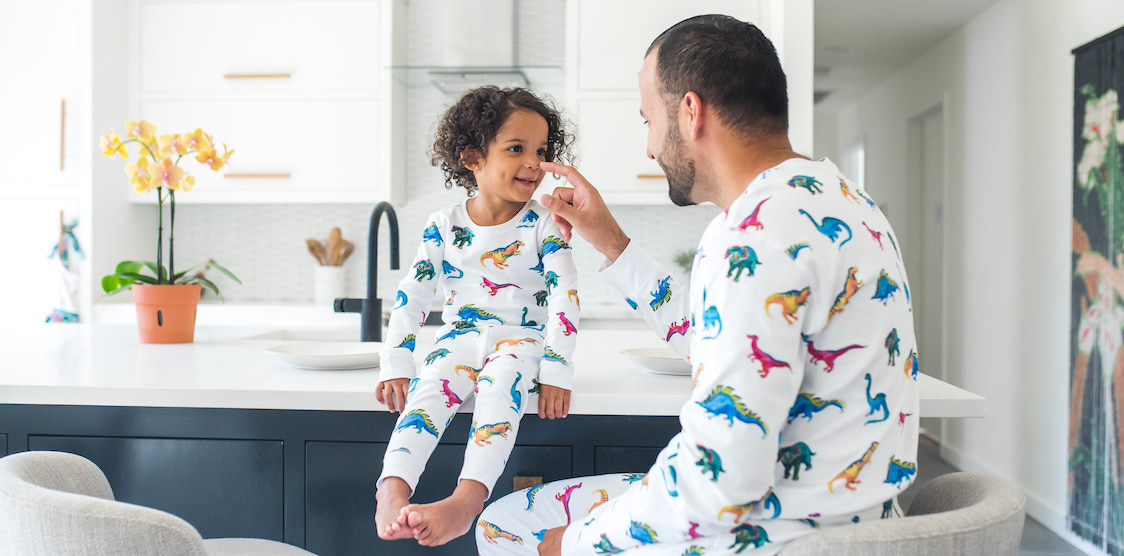A father and child wearing matching hart + land dinosaur PJs