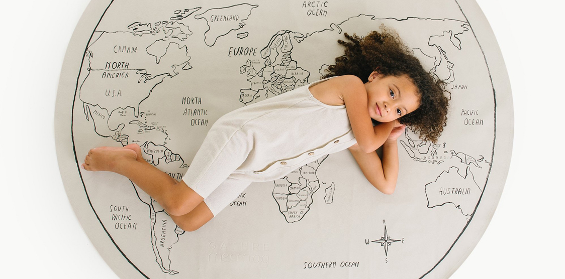 child lying on leather world map mat