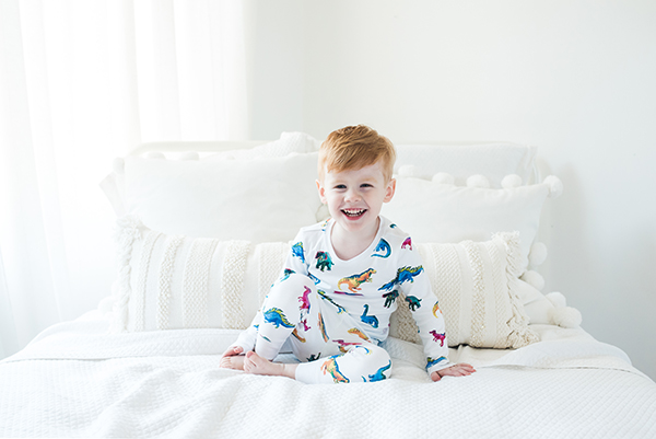 little boy on bed in dinosaur Pjs