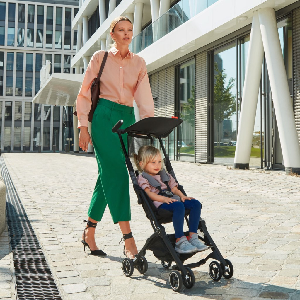 A woman pushing her child in a GB pockit stroller