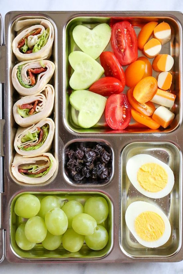 Metal lunchbox filled with fruit, veggies and wraps