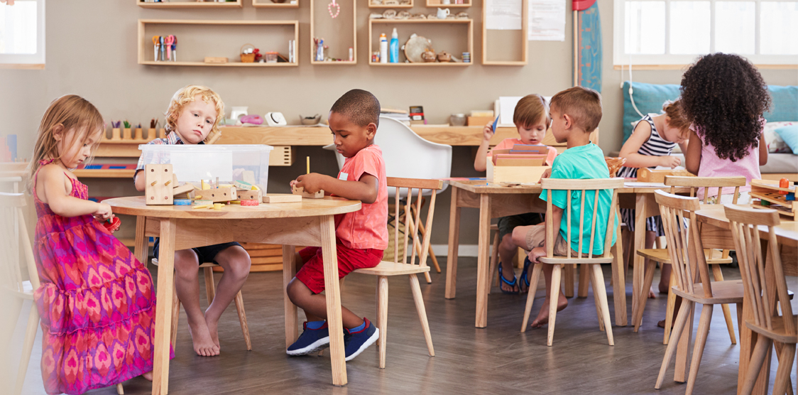 diverse kids sitting at desks in preschool