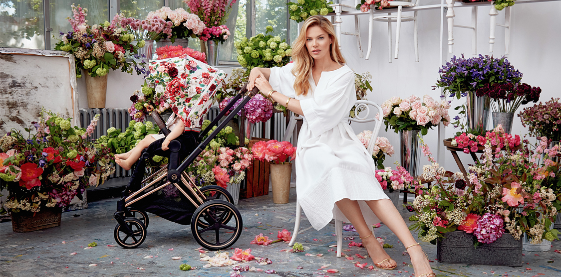 Mother sitting with baby in stroller in a florist shop