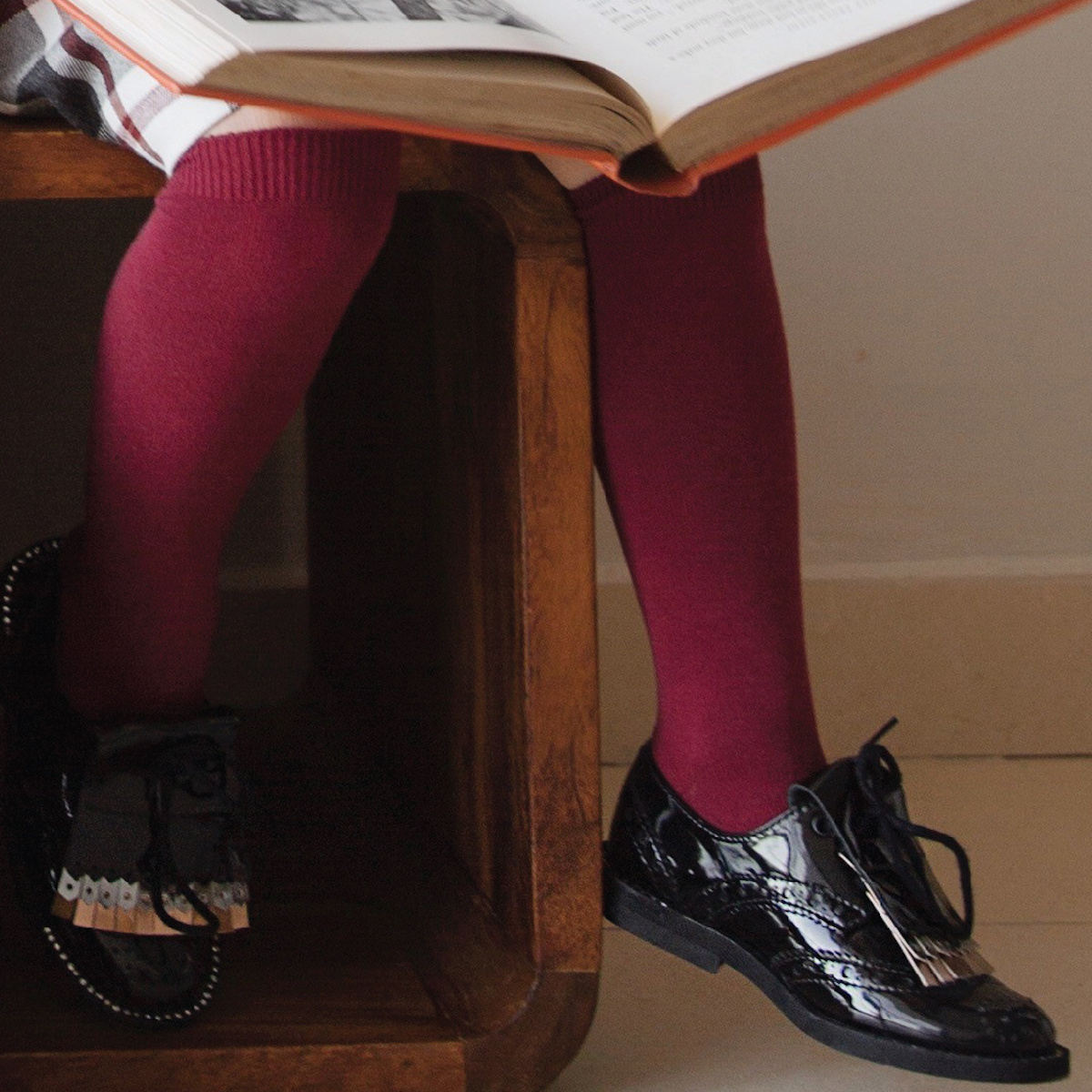 A child reading a book wearing Condor socks