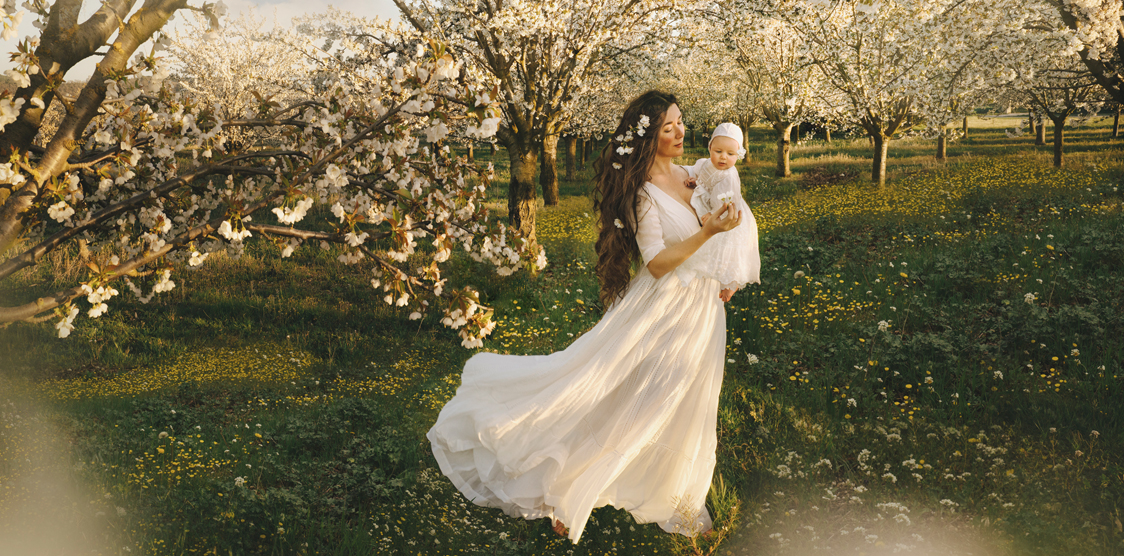 mother carrying baby through cherry blossom trees